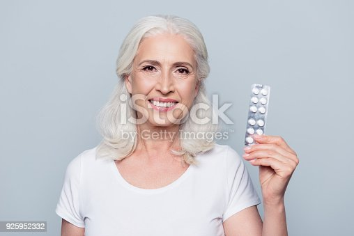 istock Pretty, attractive, nice, smiling woman present her favorite effective medical product from diseases, holding plate of tablets in hand, looking at camera over grey background 925952332