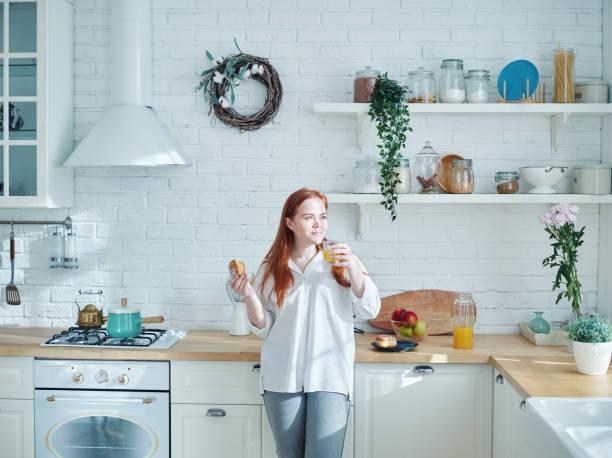 mulher nova consideravelmente autêntica com o dia vermelho do cabelo que sonha ao comer a pastelaria caseira e beber o sumo de laranja para o pequeno almoço na cozinha - body positive - fotografias e filmes do acervo