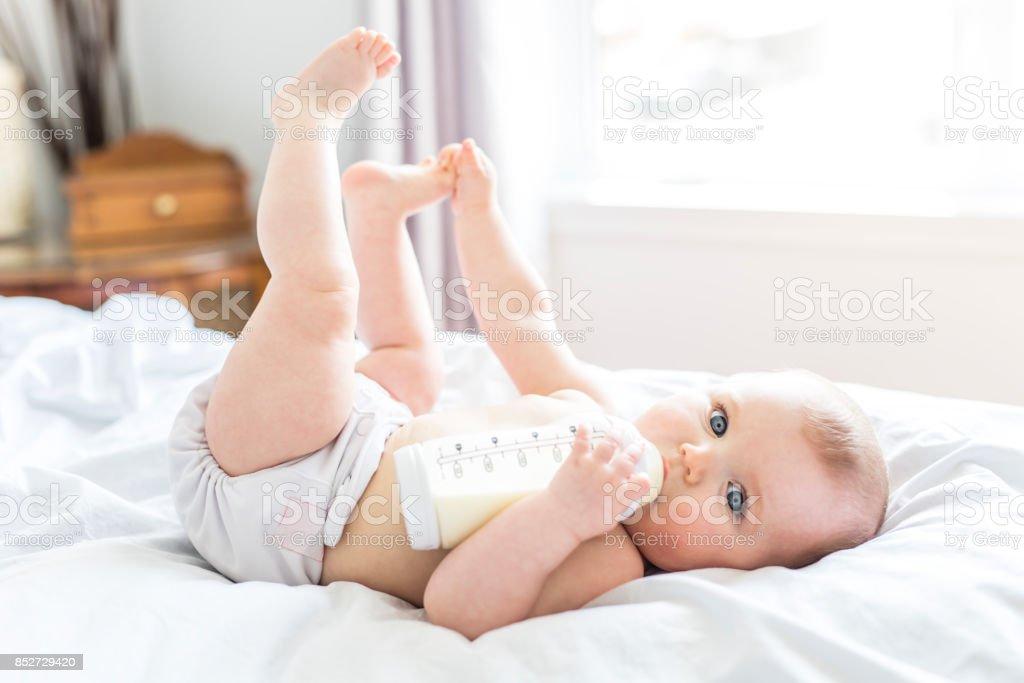 漂亮的小女孩在床上喝著瓶子裡的水。兒童穿著尿布在育嬰室圖像檔