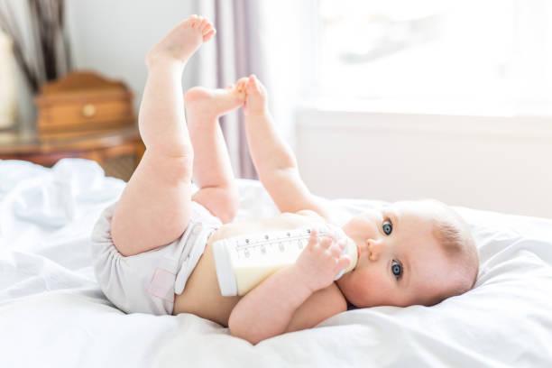 Hübsches Babymädchen trinkt Wasser aus der Flasche auf Bett liegend. Kind weared Windel im Kinderzimmer – Foto