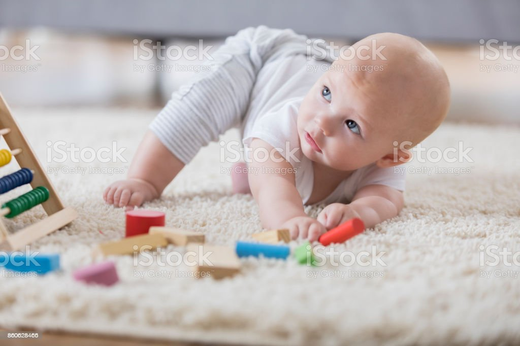 Pretty baby girl reaches for toy block stock photo