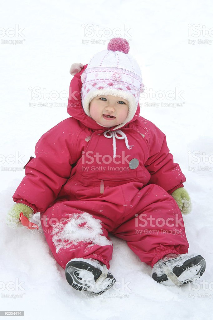 Pretty baby girl siting in the snow stock photo