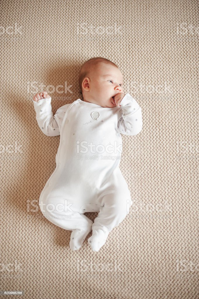 Pretty baby in a white pajamas lying on his back stock photo