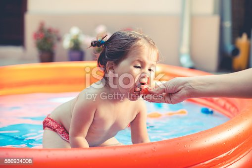 istock pretty baby is eating in the pool 586934008