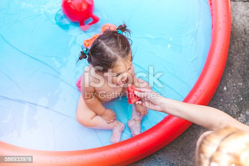 istock pretty baby is playing in the pool 586933976