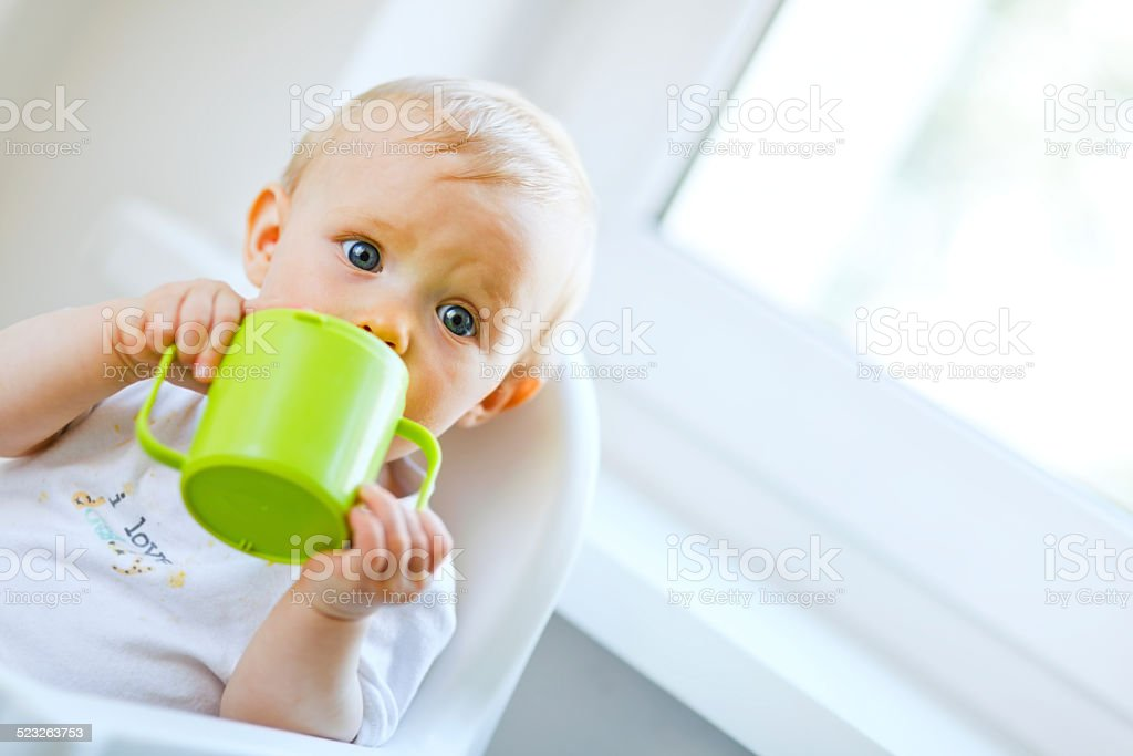Pretty baby  sitting in chair and drinking from cup stock photo