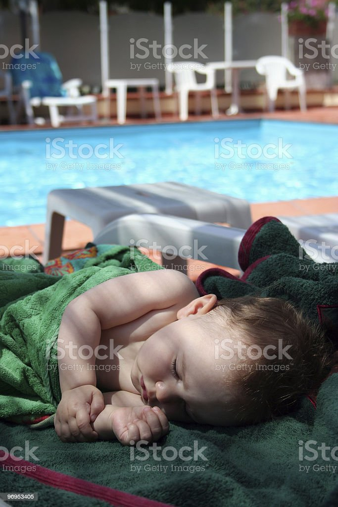 Pretty baby sleep on a bench with towels royalty-free stock photo