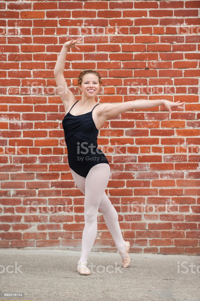 Pretty ballet girl posed in front of red brick wall stock photo