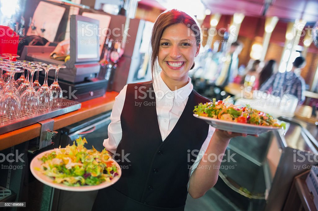 Pretty barmaid holding plates of salads stock photo