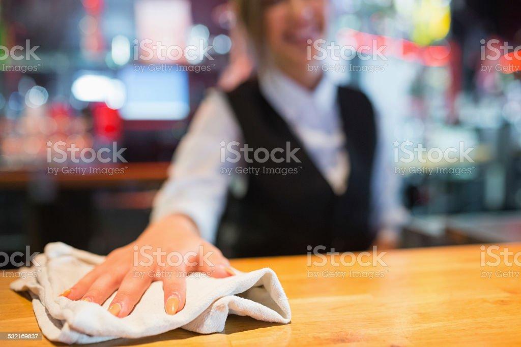 Pretty barmaid wiping down bar stock photo