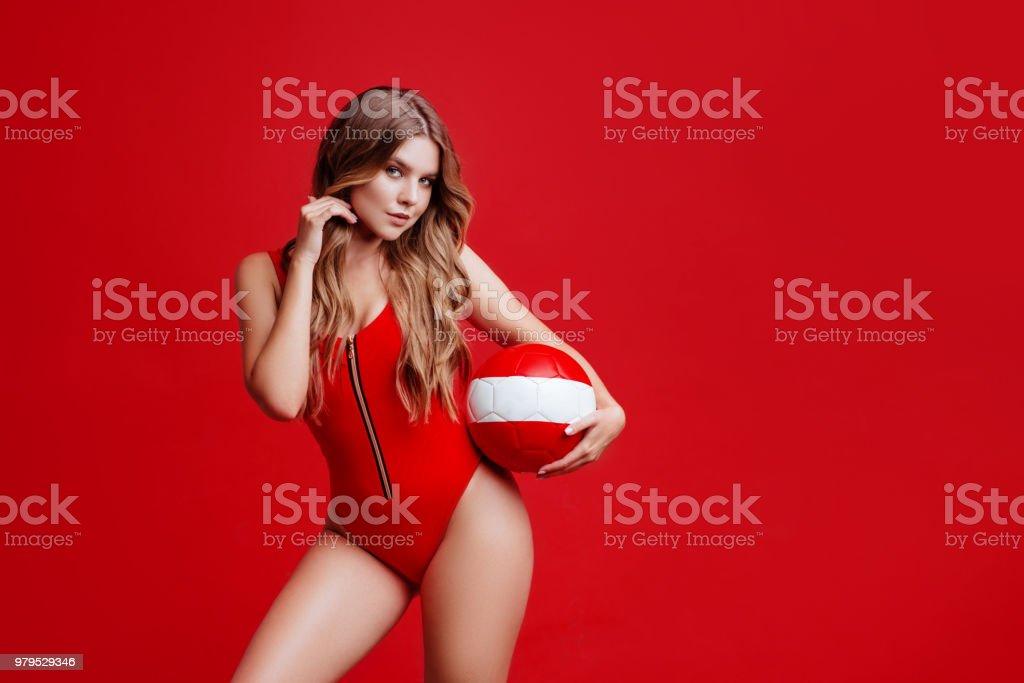 Pretty bikini model holding red ball in studio stock photo