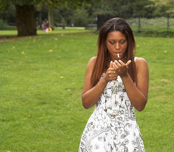 Pretty black girl lighting up her cigarette stock photo