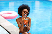 istock Pretty black lady drinking tropical beach cocktail and laughing by outdoor pool 1257703369