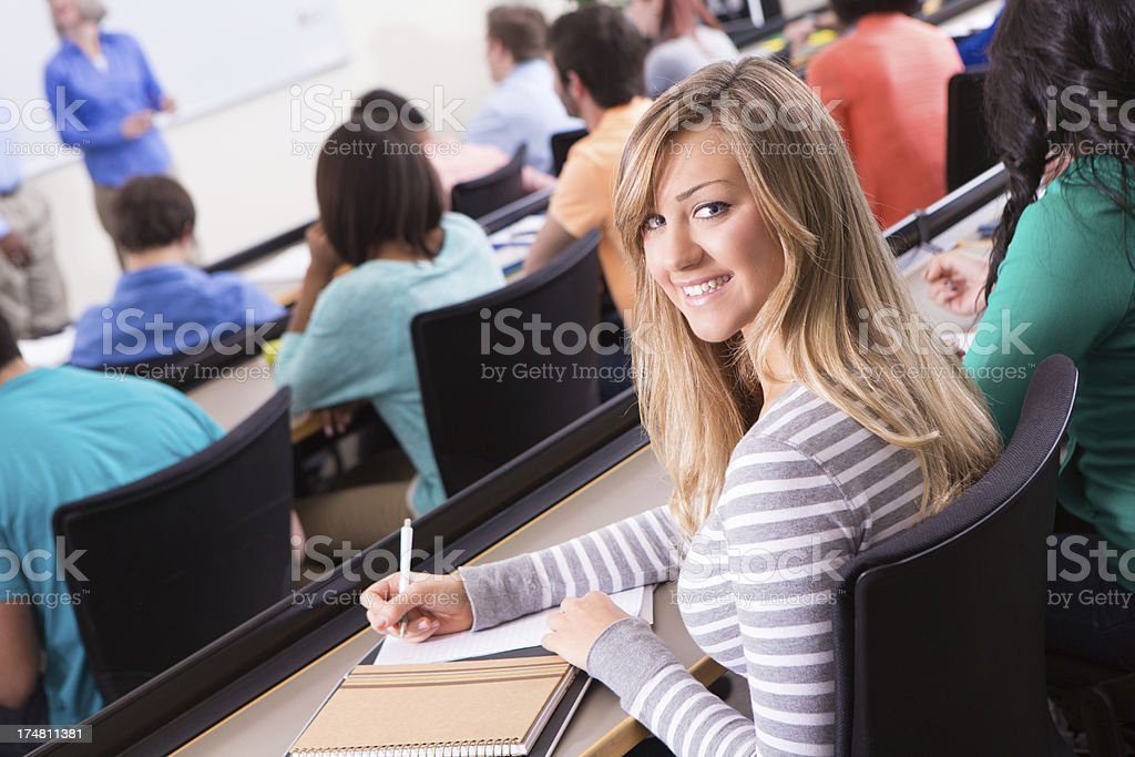 Pretty blond college student looking back, taking notes in class royalty-free stock photo