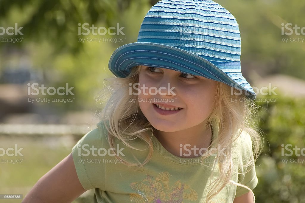Pretty blond female child wearing a turquoise sun hat royalty-free stock photo