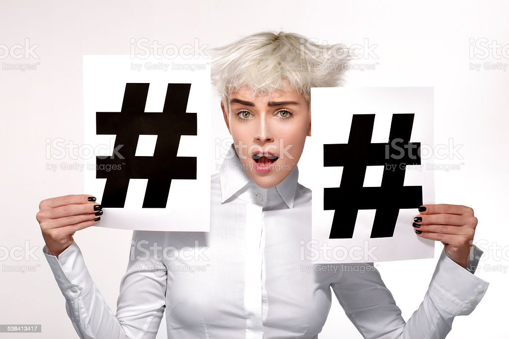 pretty blond model showing two hashtag sign on paper stock photo