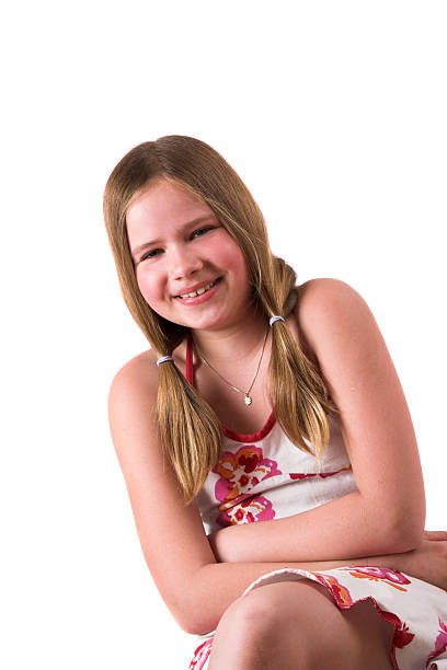 Pretty blond ten year old sitting and laughing stock photo