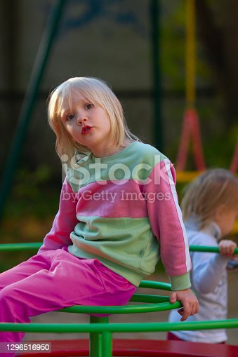 Pretty blond toddler girl wearing fancy sport costume sitting on carusel on the playground on a sunny day