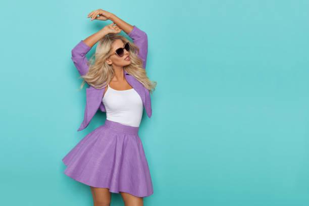 hübsche blonde frau posiert mit erhobenen armen - lange jacken stock-fotos und bilder