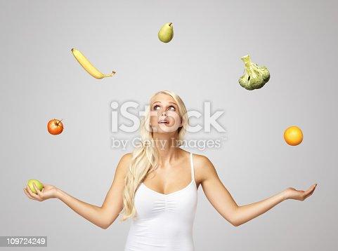 istock Pretty blond woman juggling fruits 109724249