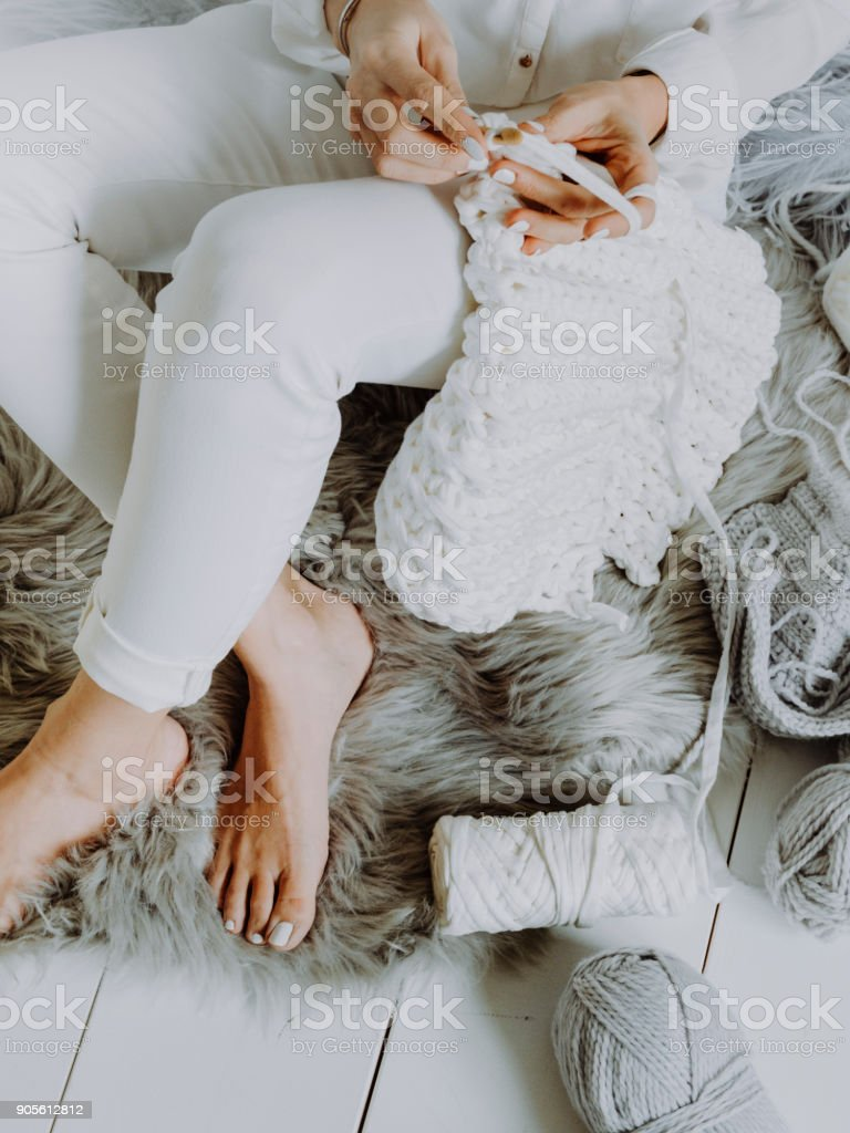 pretty blond young woman sitting on wooden floor and crocheting with white wool stock photo