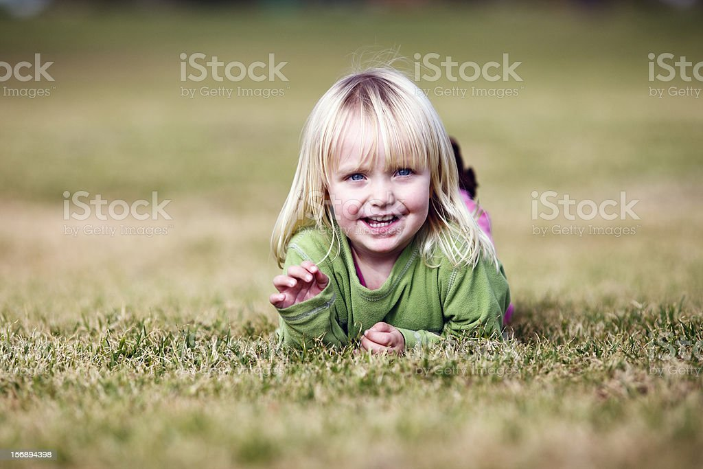 Pretty blonde 3 year old girl lies in grass, playing stock photo