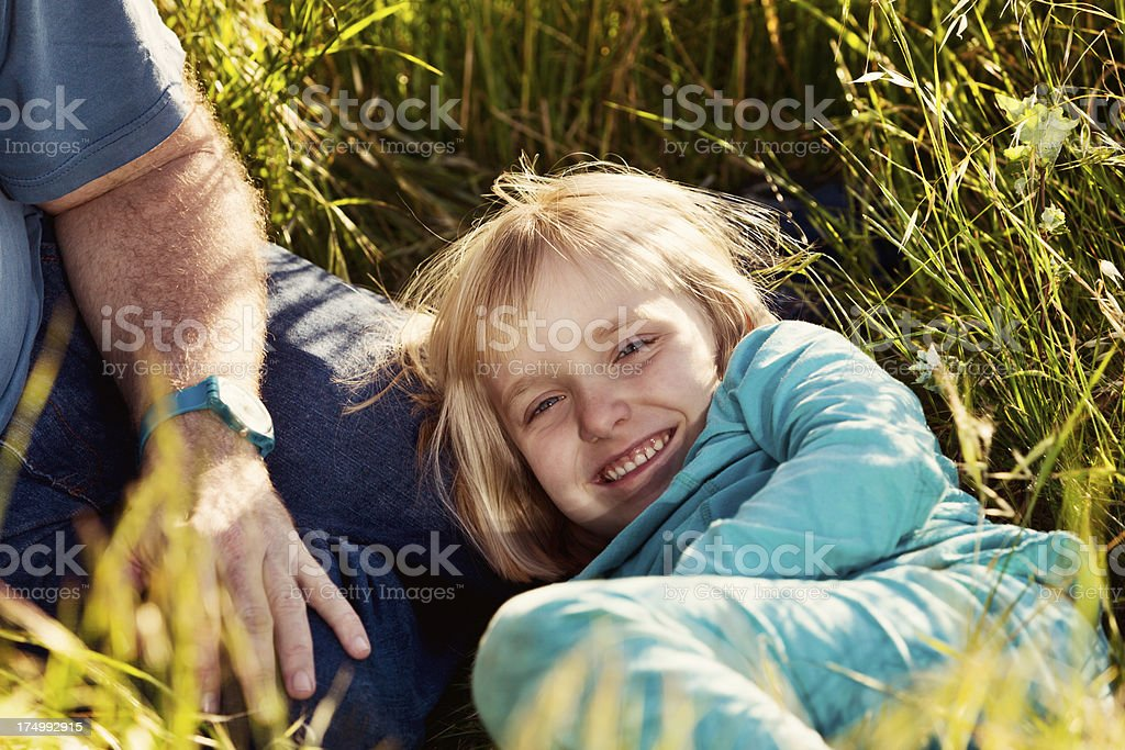 Pretty blonde 5-year-old playing in long grass with her dad stock photo