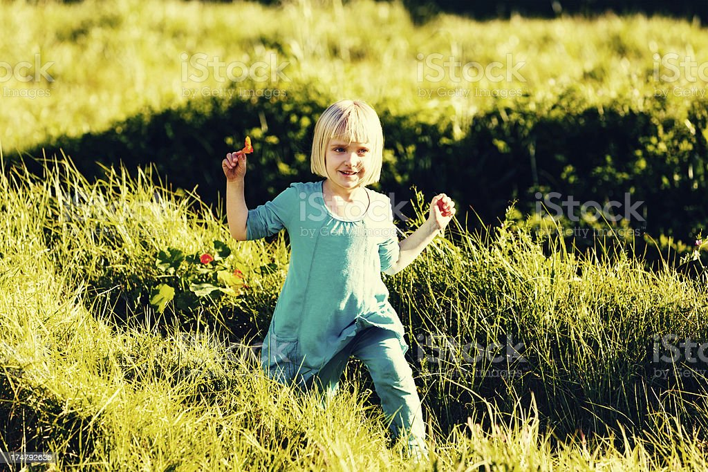 Pretty blonde 5-year-old running through meadow stock photo