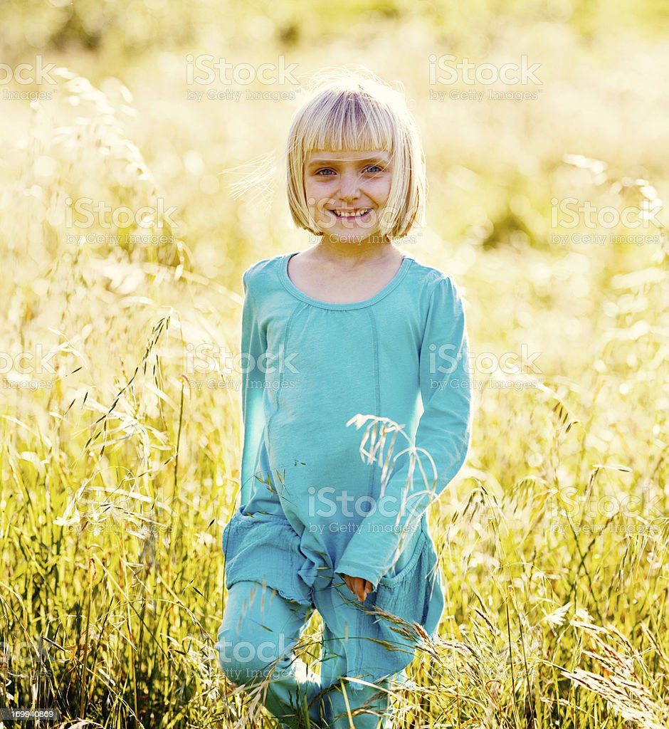 Pretty blonde 5-year-old runs through grassy field, smiling stock photo