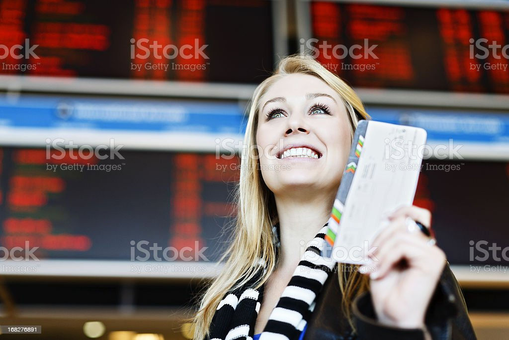 Pretty blonde at airport holding boarding pass looks up smiling royalty-free stock photo