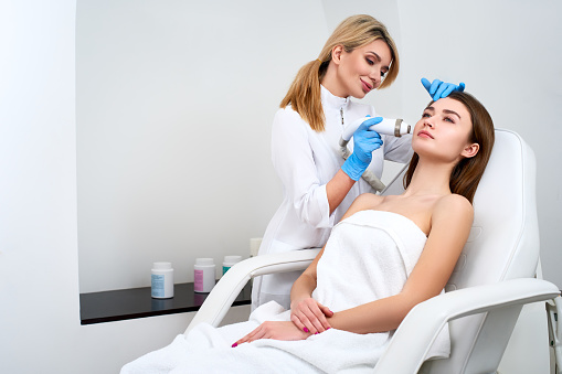 istock Pretty blonde beautician doctor doing rf-lifting procedure for woman laying in a beauty salon. Hardware cosmetology. Patient receiving electric facial massage. Skin rejuvenation and wrinkle smoothing 1145814513