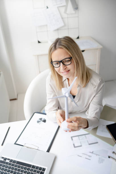 pretty blonde business woman is sitting in her office working on new alternative energy development looking at a model of a wind turbine stock photo