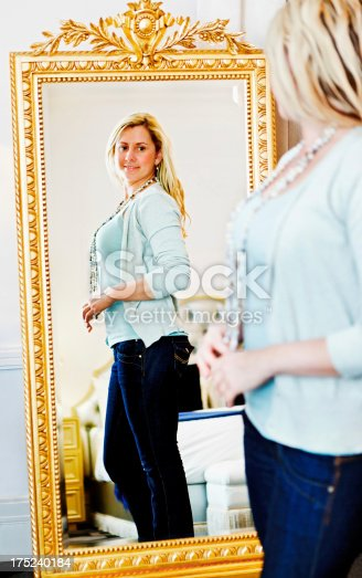istock Pretty blonde checking her reflection in full-length mirror 175240184