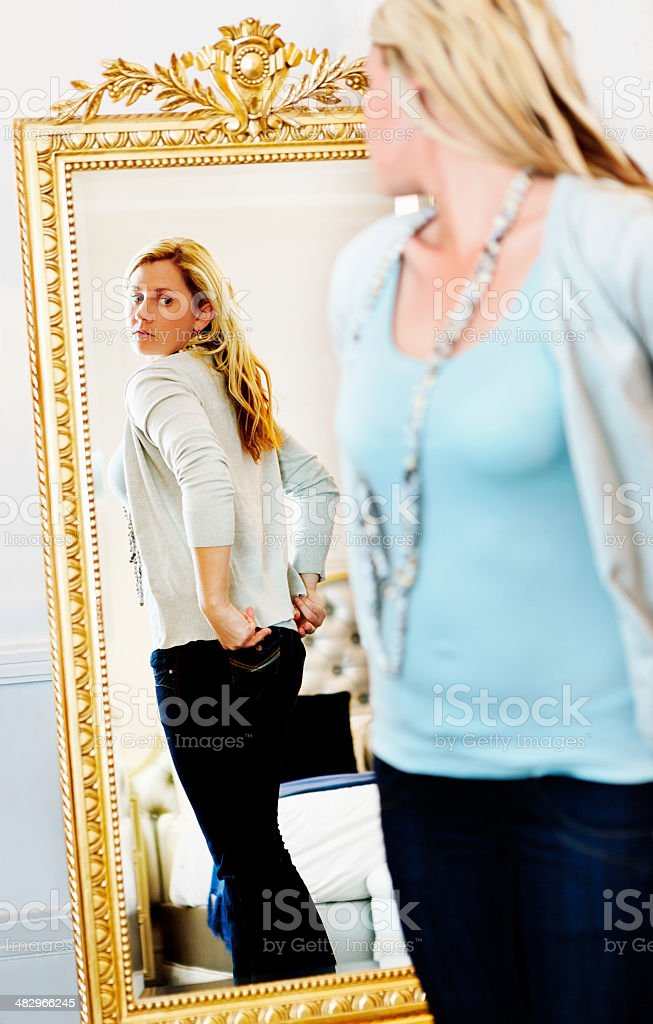 Pretty blonde checking rear view in mirror stock photo