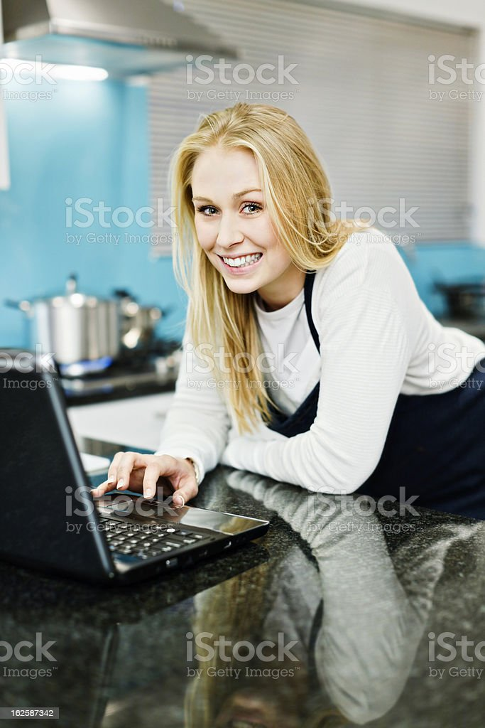 Pretty blonde cook in apron using laptop on kitchen counter royalty-free stock photo