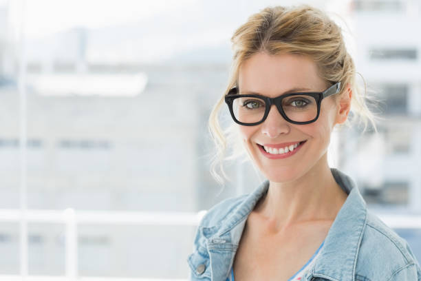 Pretty blonde designer smiling at camera stock photo