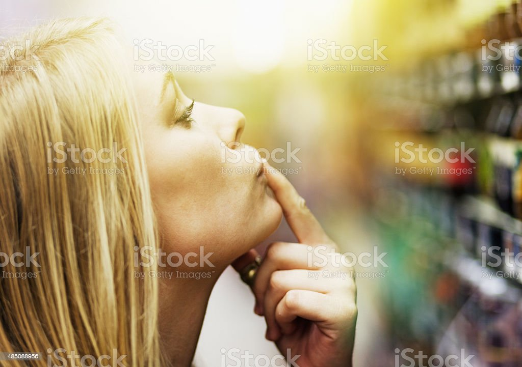 Pretty blonde, finger on lip, choosng product from supermarket shelf stock photo