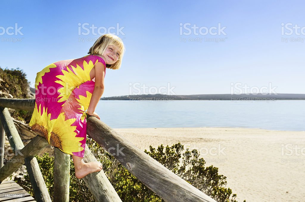 Pretty blonde girl at beach looks over shoulder smiling stock photo