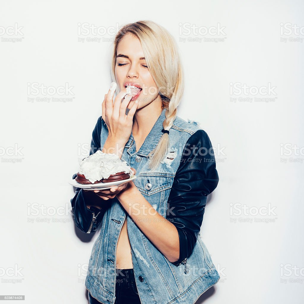 Pretty blonde girl  eating chocolate Cake Pretty blonde girl eating chocolate Cake. Indoor lifestyle portrait of woman in sunglasses.  White background, not isolated Adult Stock Photo