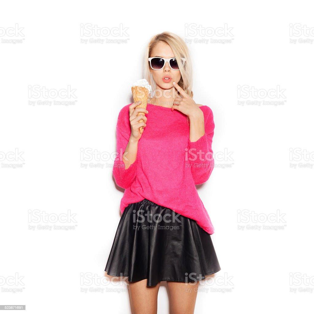 Pretty blonde girl  eating ice cream stock photo