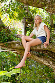 A pretty young blonde preteen sitting in a banyon tree thinking.