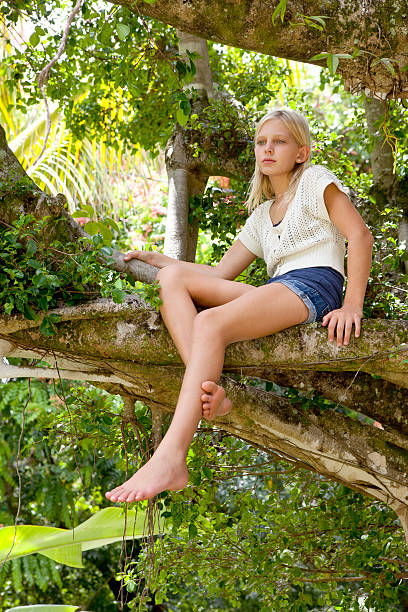 Pretty Blonde Girl in a Banyon Tree stock photo