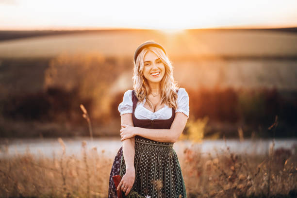 Pretty blonde girl in dirndl, standing outdoors in the field, holding bouquet of a field flowers. Pretty blonde girl in dirndl, traditional festival dress, standing outdoors in the field at sunset time, holding bouquet of a field flowers. Oktoberfest, St. Patrick's day, international beer day concept sun shining through dresses stock pictures, royalty-free photos & images