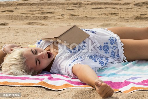 chica joven y bonita bosteza mientras lee en la playa
