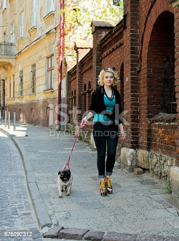 istock Pretty blonde girl walking with funny pug 675292312