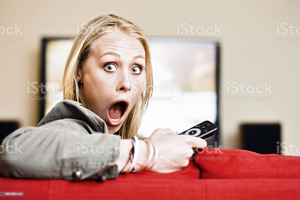 Pretty blonde holding remote  looks totally shocked - what's showing? royalty-free stock photo