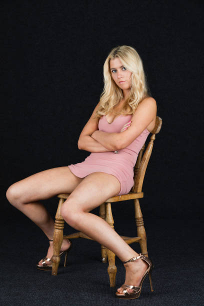 pretty blonde looking bored and annoyed - mini dress stock photos and pictures