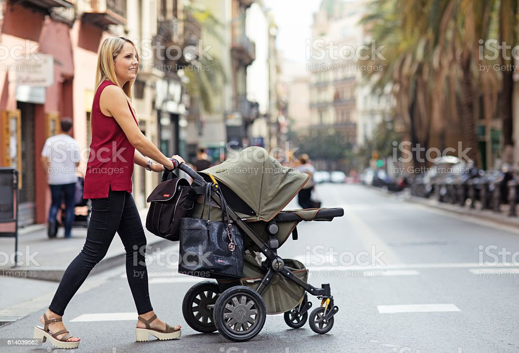 Pretty blonde mother walking in southern european city with pushchair - foto de stock