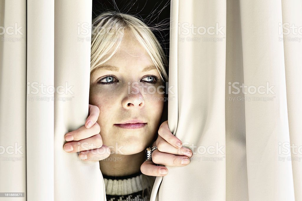 Pretty blonde peeps sideways through closed curtains, smiling royalty-free stock photo
