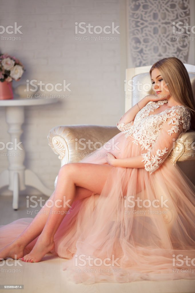 cc847c2d6 Pretty blonde pregnant young girl with fashion makeup is wearing luxury  pink lingerie dress at home in cozy interior with bouquet of roses flowers  - Stock ...